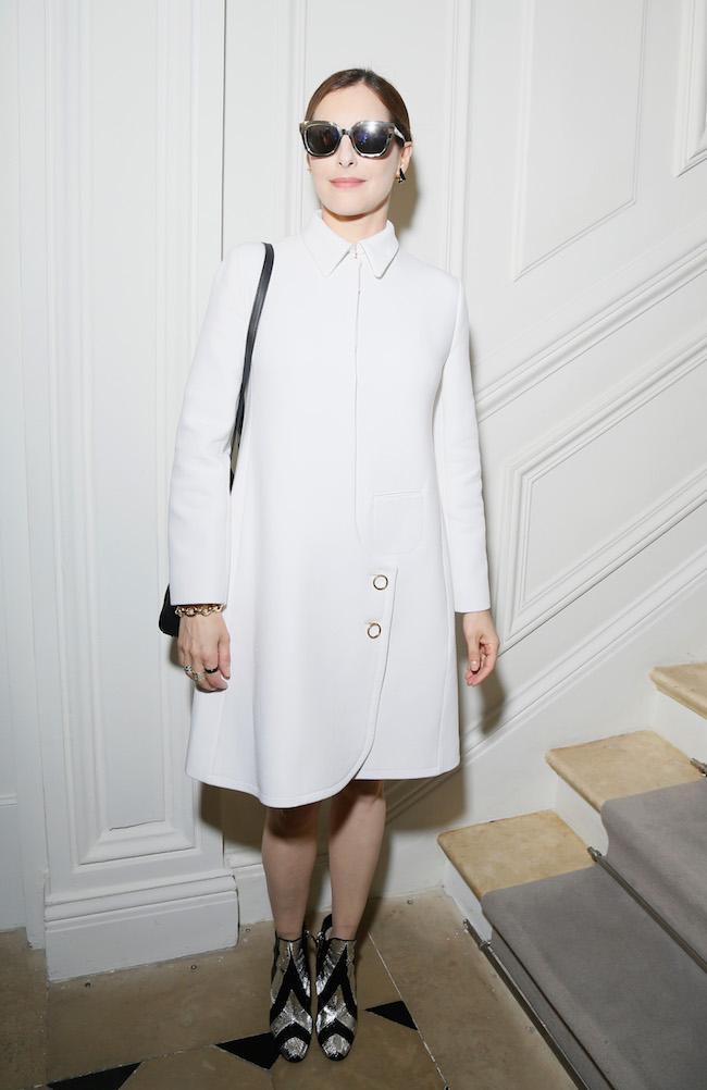 Amira Casar porte un manteau en laine écrue Dior. Amira Casar is wearing an ecru wool coat Dior