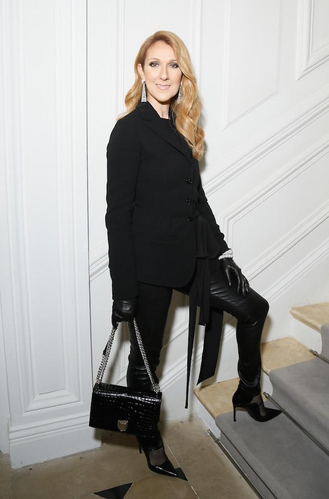 Céline Dion porte une veste Bar en crepe de soie noir, un pantalon en cuir noir, souliers et sac Dior. Céline Dion is wearing a black crepe silk Bar jacket, black leather pants, shoes and bag Dior.
