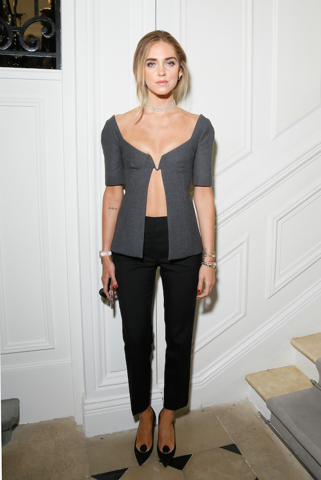 Chiara Ferragni porte un top en laine grise avec un pantalon en crêpe de soie noir et souliers Dior. Chiara Ferragni is wearing a light grey wool top, crepe silk black pants and shoes Dior.