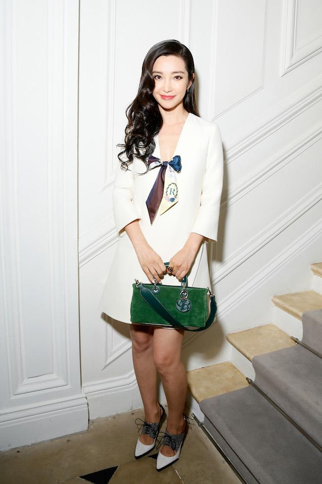 Li Bing Bing porte une robe en crêpe de soie écru, foulard en soie, sac et souliers Dior. Li Bing Bing is wearing a off white crepe silk dress, a silk scarf, bag and shoes Dior.